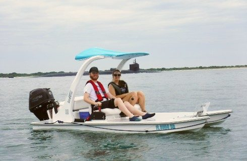 Two people in a small backwater cat boat out on the open water