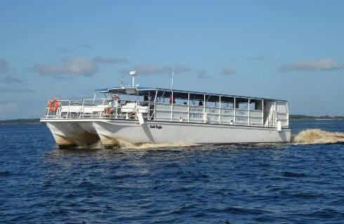 Large white river cruise boat out on the open water with blue skies above