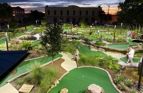 Overhead view of a large mini golf resort with buildings and sunset sky in the background