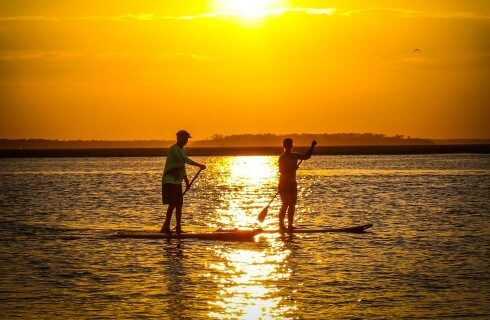 Two people on stand up paddle boards out on the open water during sunset