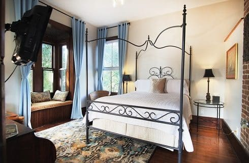 Elegant bedroom featuring bed with tall ornate headboard, gold linens and two bright windows flanked with curtains