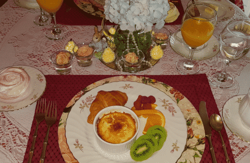 Floral plate with egg dish, fruit and croissant on table with lace tablecloth, coffee and orange juice