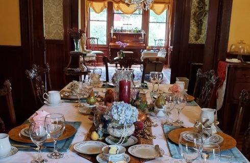 Elegant dining room with antique brown chairs and table set with fine china, with sitting room in background