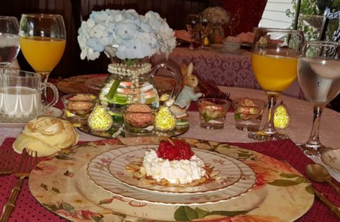 Round dining table set with floral dinnerware, displaying breakfast with coffee, water and orange juice