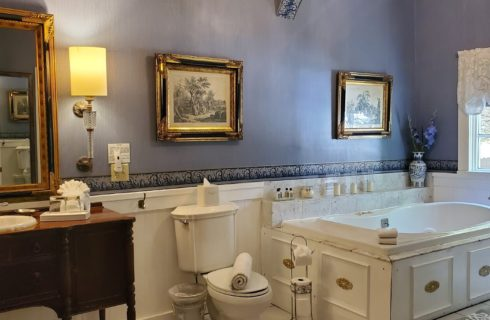 Large bright bathroom with antique vanity, jacuzzi tub and blue walls with large pieces of artwork