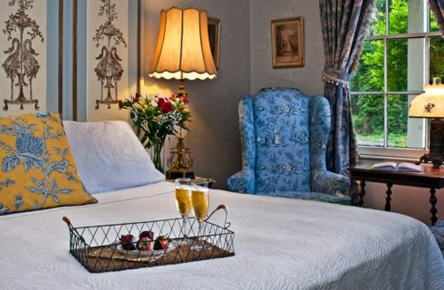 Bed with white comforter and tray with champagne flutes and strawberries next two blue chairs below large window