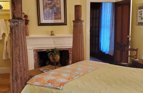Bedroom with four poster bed, fireplace, table with lamp and closet with two plush white robes hanging