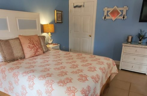 Bright bedroom with blue walls featuring white queen bed, wicker dresser and TV on the wall