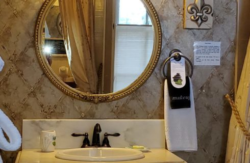 Vanity with sink, round gold mirror and decorative wallpaper with white plush robe