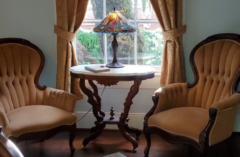 Two antique upholstered chairs with round side table in front of bright window