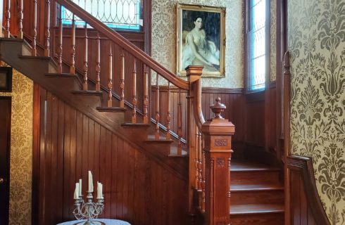 Elegant staircase in a historic home with decorative wallpaper, stained glass windows and art on the wall