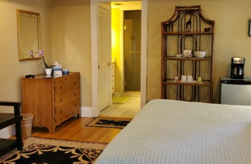 Spacious bedroom with queen bed, sitting bench, TV, dresser, hutch and doorway into bathroom