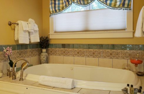 Large jacuzzi tub under a bright window with vase of flowers, tray with toiletries and plush folded towels