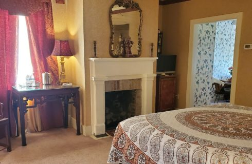 Bedroom featuring queen bed with multi-colored quilt, chair and desk, fireplace and doorway into separate sitting room