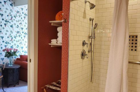 Tall shower with white subway tile, linen closet and doorway into sitting room with flowered wallpaper