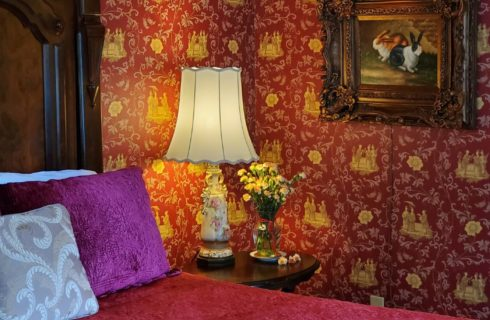 Queen bed with red coverlet, dark wood bedside table and walls with red and yellow ornate wallpaper