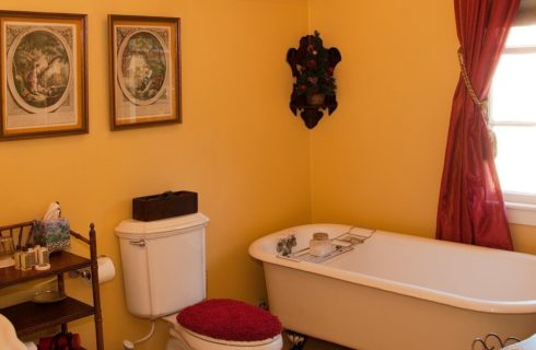 Bathroom with clawfoot tub underneath large bright window, with toilet and pedestal sink