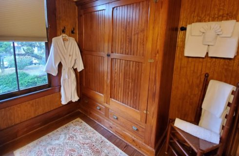 Bathroom with dark wood paneled walls, bright window and plush white robe and towels