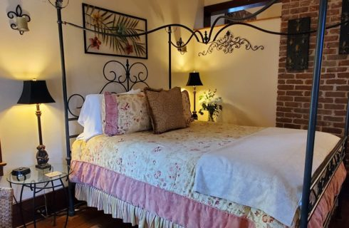 Black wrought iron four poster canopy bed with pink and white quilt in cozy guest room with brick wall