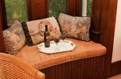 Bay window sitting area with African animal themed pillows and tray with wine bottle and two glasses of red wine