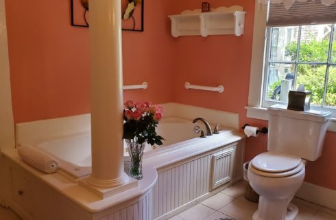Large jacuzzi tub in bright bathroom with tall white column, pink walls and vase of pink roses