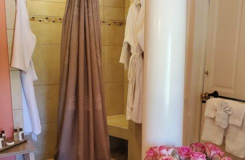 Bathroom with tall open shower, folded white towels, tray of toiletries and vases with pink roses