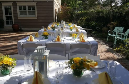 Four white tables outdoors, set for a wedding with yellow flowers and napkins and white lanterns