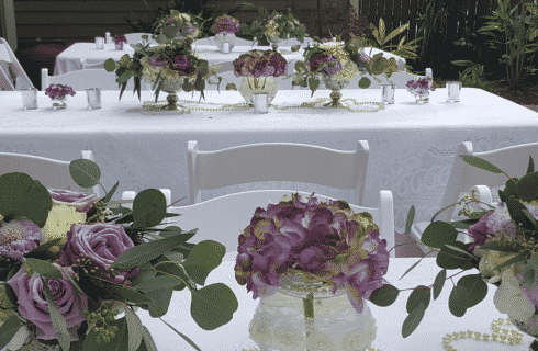 Three white tables outdoors, set for a wedding with numerous vases of lilac and purple flowers
