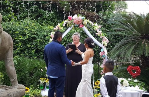 Bride and groom standing in front of an officiant under a flower-covered arch