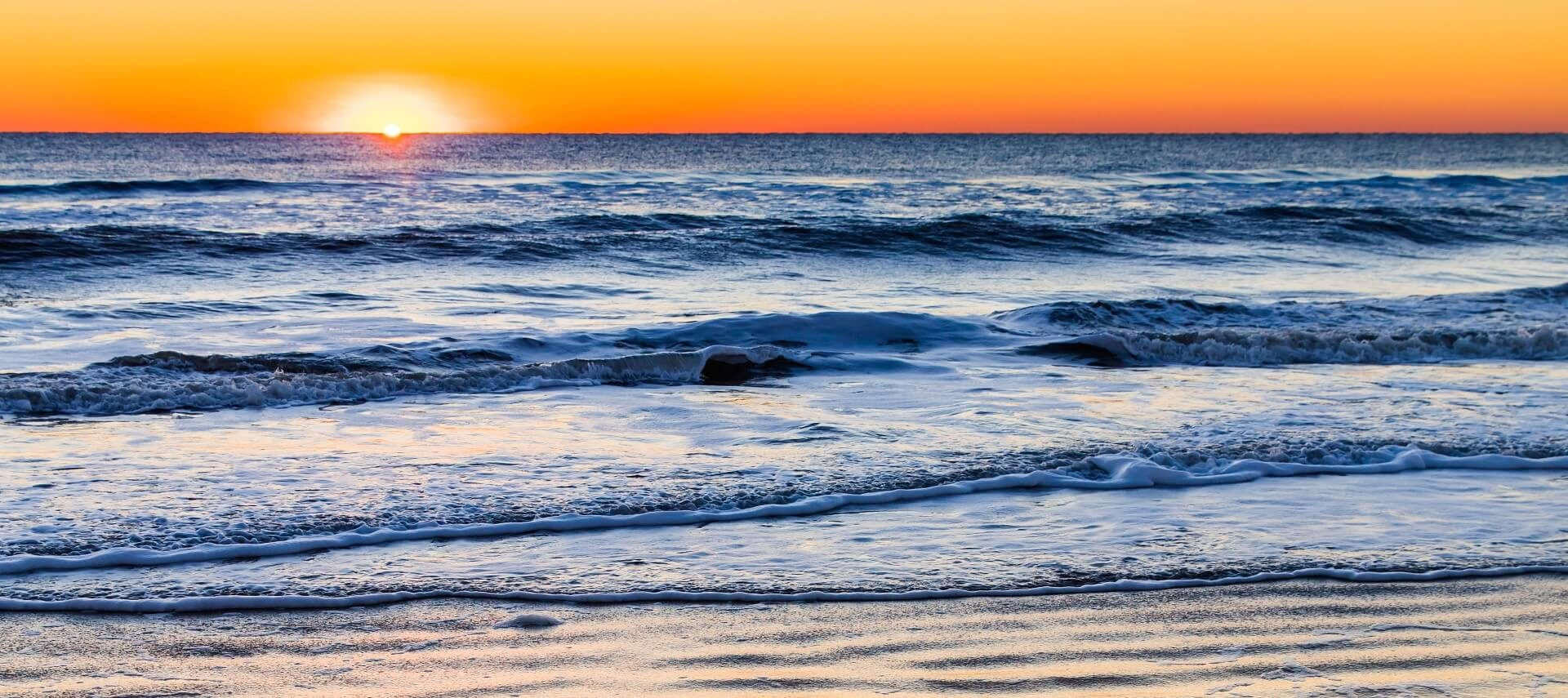 Bright yellow and orange sunset over ocean waters with soft waves breaking on the shore