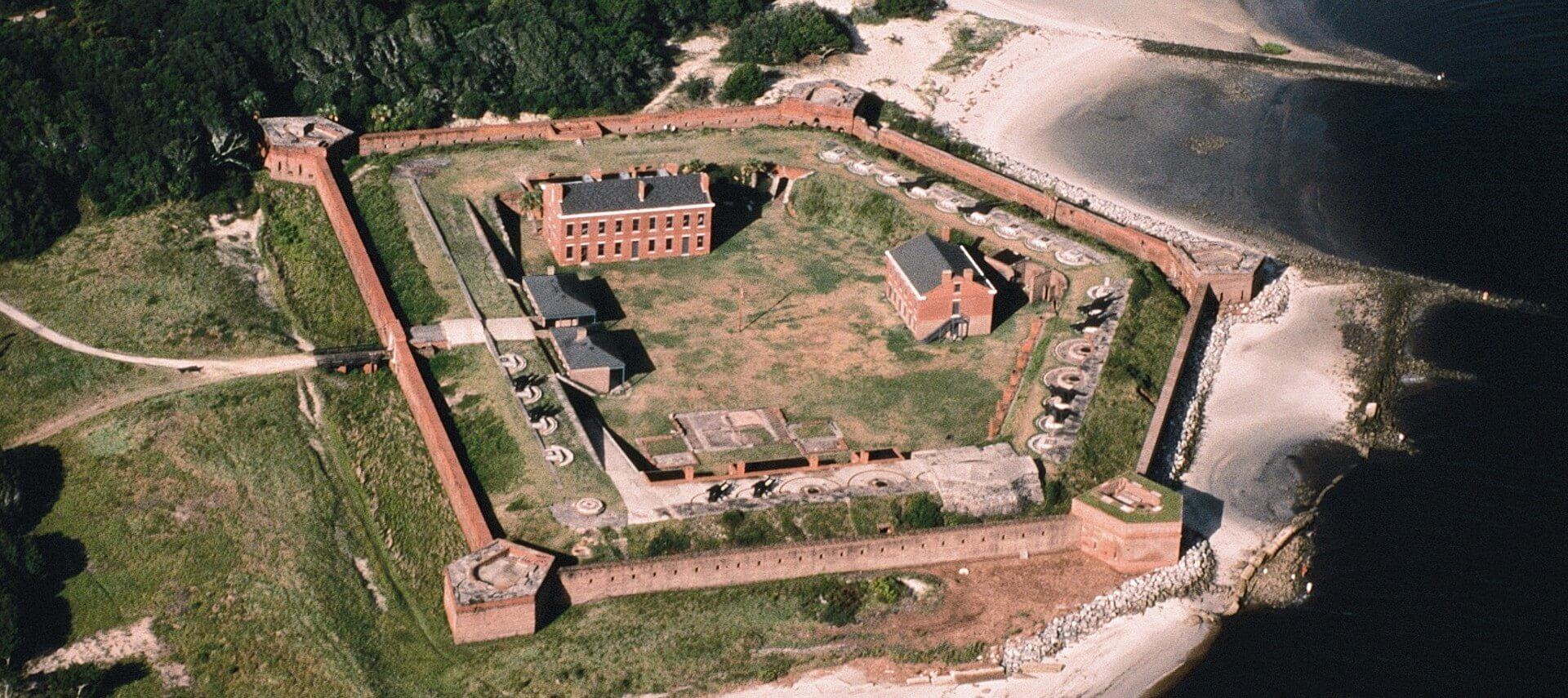 Overhead drone view of a large historic fort next to the ocean and and forested area