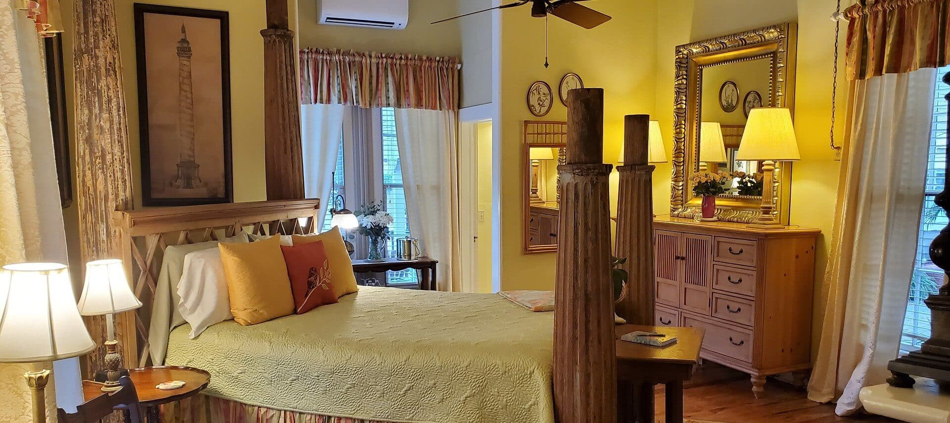 Four poster bed in room with brown accent furniture, yellow walls and bright and airy windows