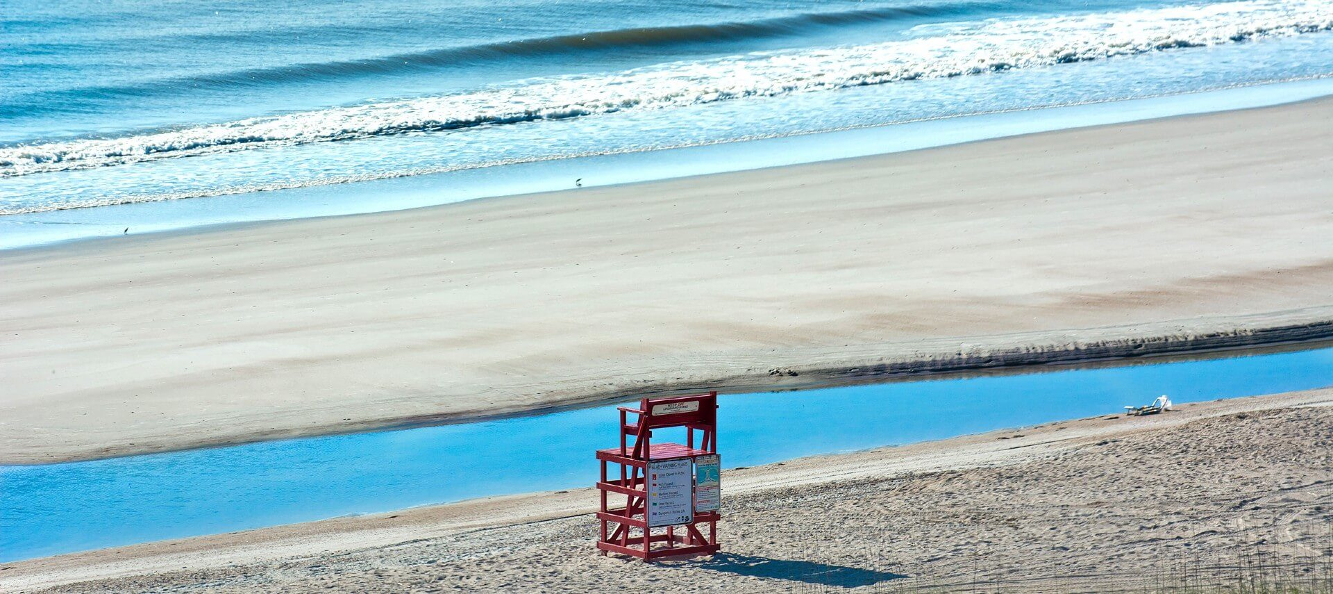 Solitary red lifeguard chair on the beach facing calm blue ocean waters