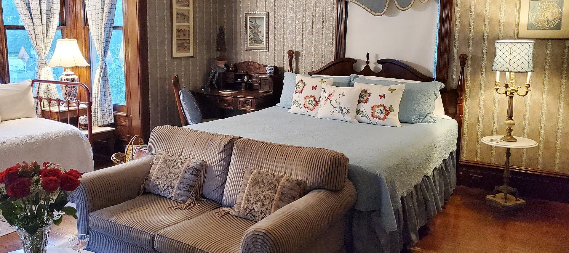 Large bright bedroom featuring queen bed, loveseat and coffee table, daybed and antique writing desk