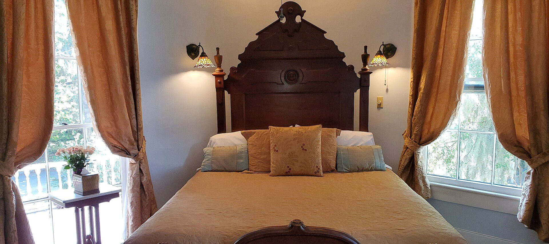 Gorgeous queen bed with tall mahogany headboard and gold linens next to two large bright windows
