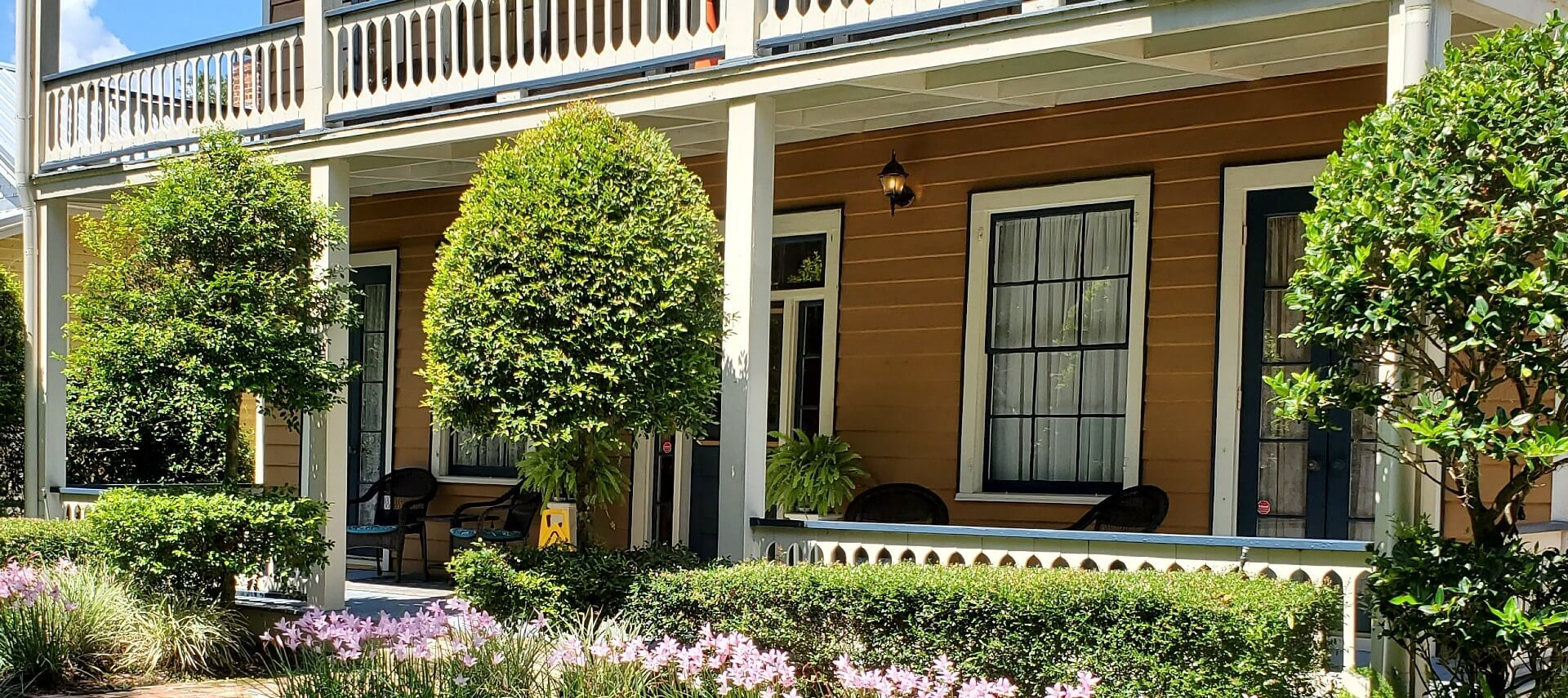 Front facade of a two story home with large black and white windows, porch with wicker furniture and lush landscaping