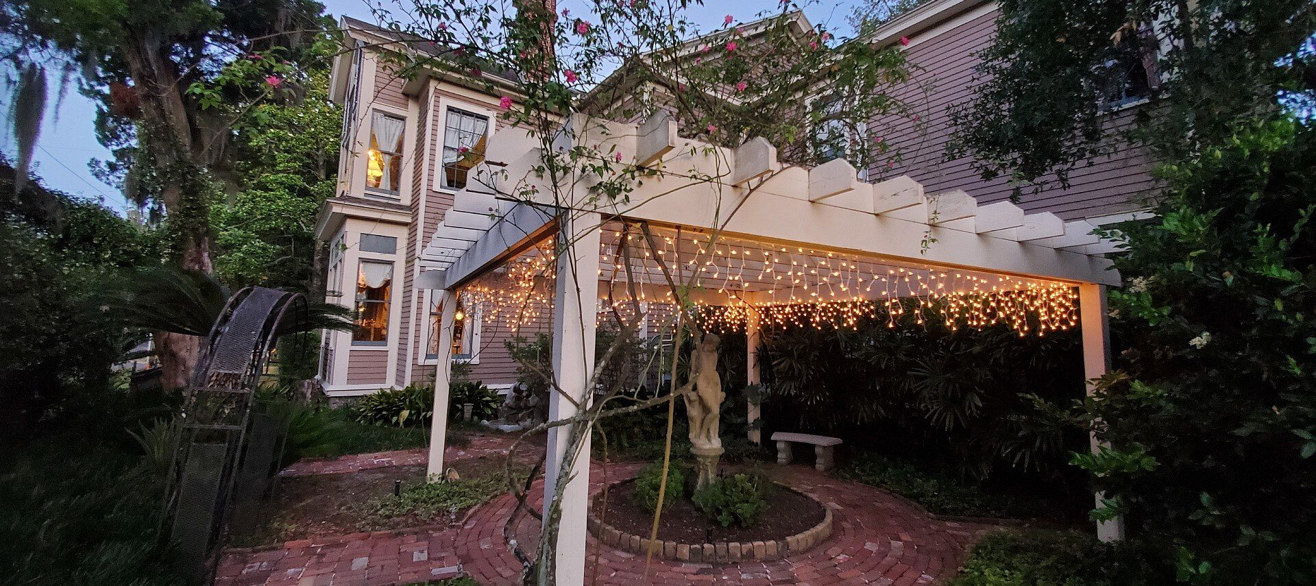 Back patio of a large home featuring a white pergola covered with dangling white lights over a statue