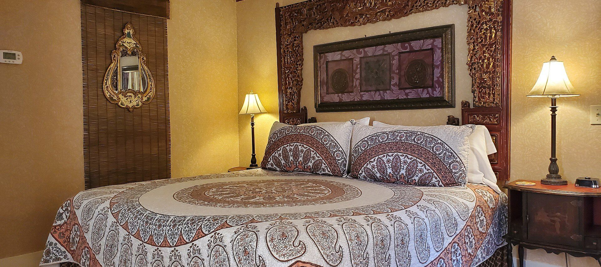 Bedroom with quilt-covered bed, unique wooden headboard and bedside tables with lamps