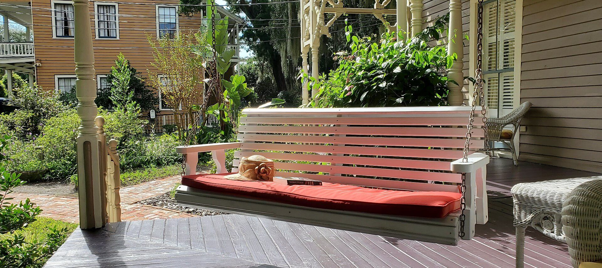 Wooden swinging bench with red cushion at the corner of a large patio with lush greens all around