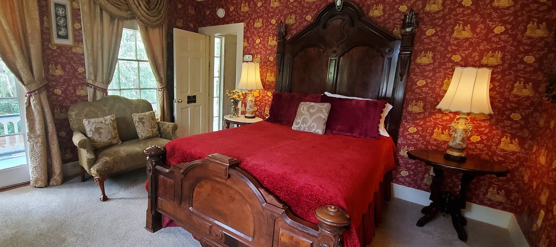 Stunning mahogany queen bed in room with red and yellow ornate wallpaper, loveseat and two bright windows