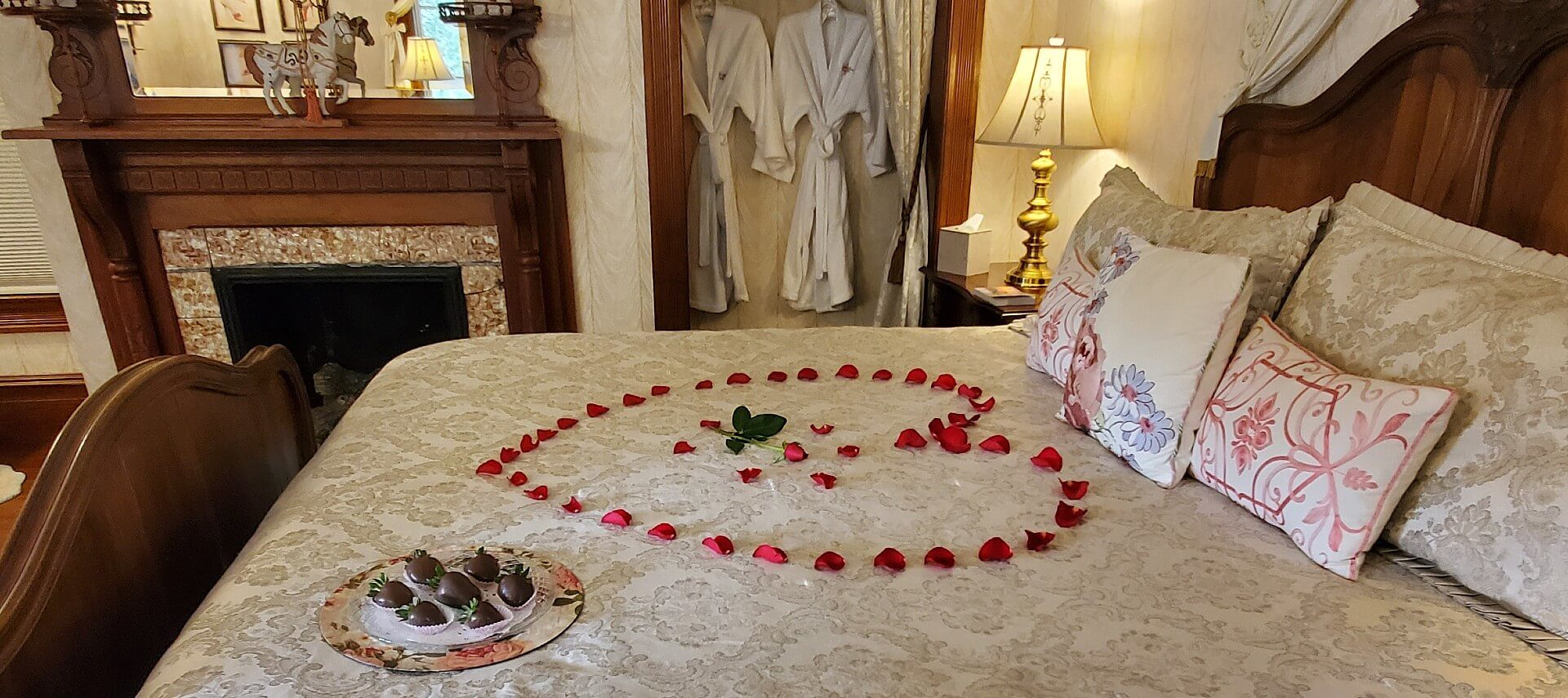 Guest room with dark wood furniture, fireplace and rose petals in the shape of a heart on the bed.