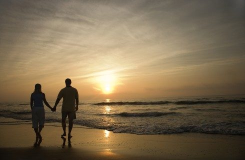 Two people holding hands walking along the shore of a beach at sunset