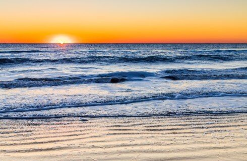 Soft waves coming onto shore under a glowing orange sunset