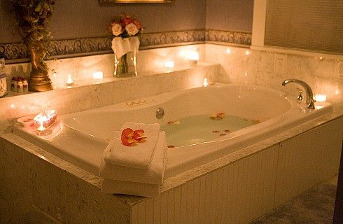 Large jacuzzi tub featuring folded white towels, rose petals and lit candles